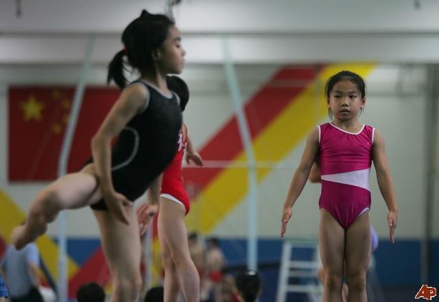 Young chinese girls practice on beams during gymnastics training at