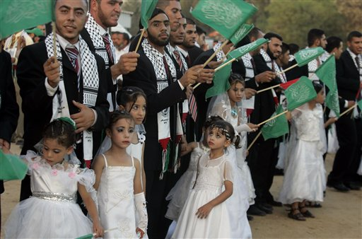 Palestinian girls stand in front of a line of grooms during a mass wedding ceremony in Beit Lahiya, northern Gaza Strip, Thursday, July 24, 2008. More than 100 couples took part in the event which was organized by the Islamic Association. (AP Photo/Hatem Moussa)